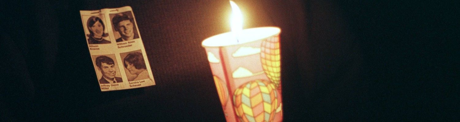A student holding vigil with a candle in hand