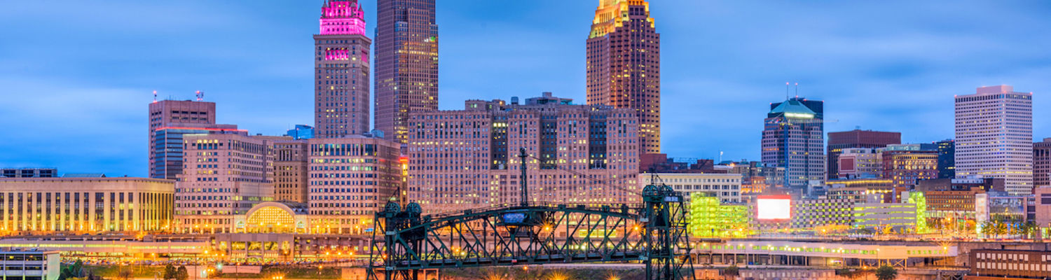The Cleveland skyline at twilight with Terminal Tower glowing pink, as seen from the Scranton Flats, with the Cuyahoga River and Eagle Avenue Bridge in the foreground.