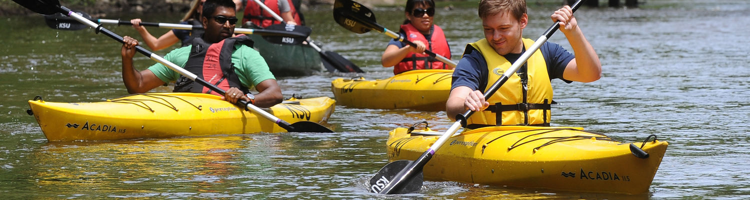 Students paddle down the Cuyahoga River in kayaks on a sunny day