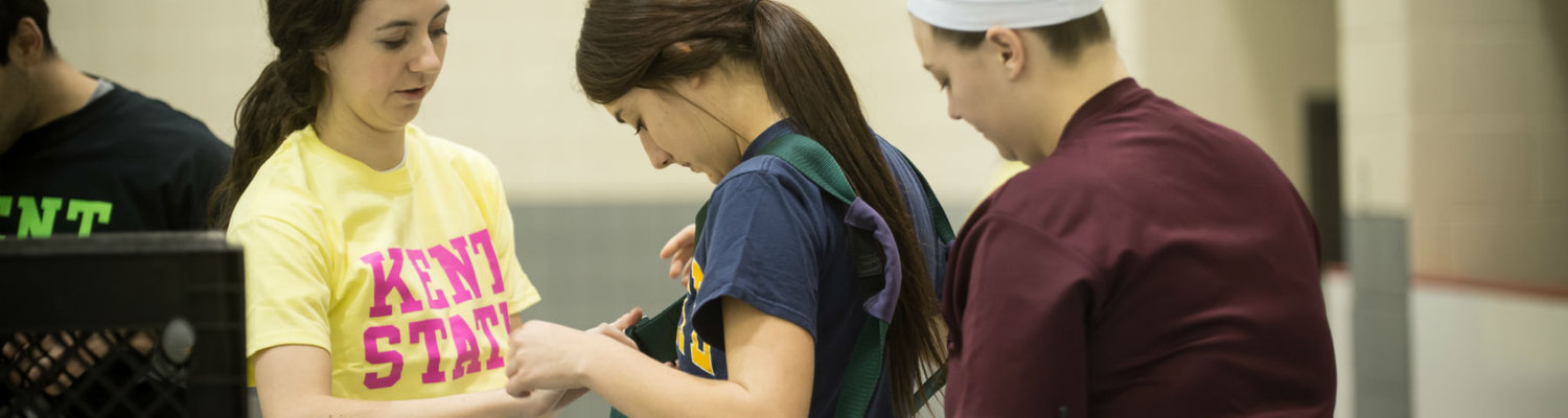 Two students help another put on a protective vest at the Student Recreation and Wellness Center