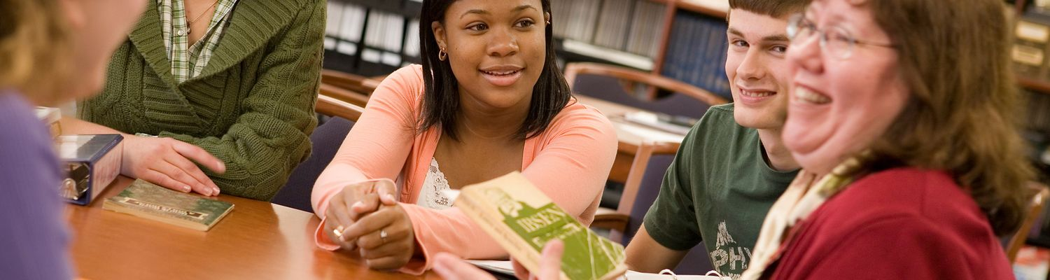 A Freshman Honors Colloquium instructor discusses a book with her students.