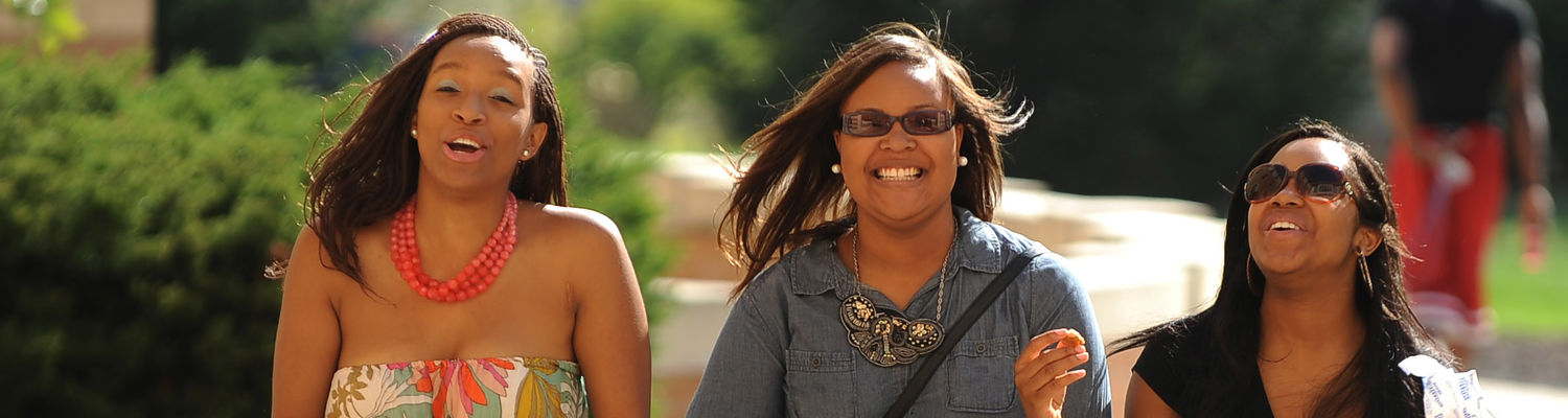 A group of students share a laugh while walking by Centennial Courts on a bright, sunny day