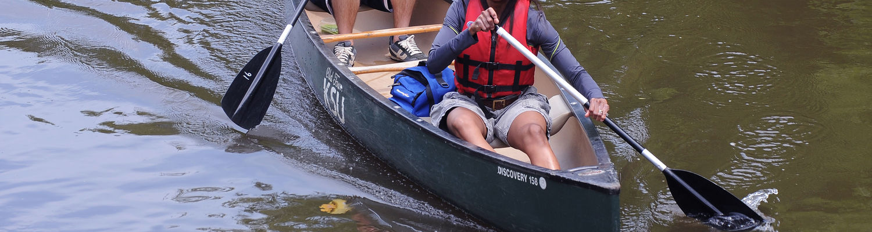 A couple students wearing life jackets paddle a kayak
