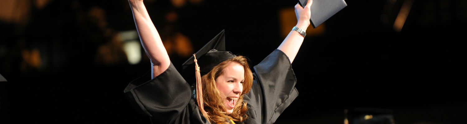 A student raises her hands in celebration after graduating from Kent State University.