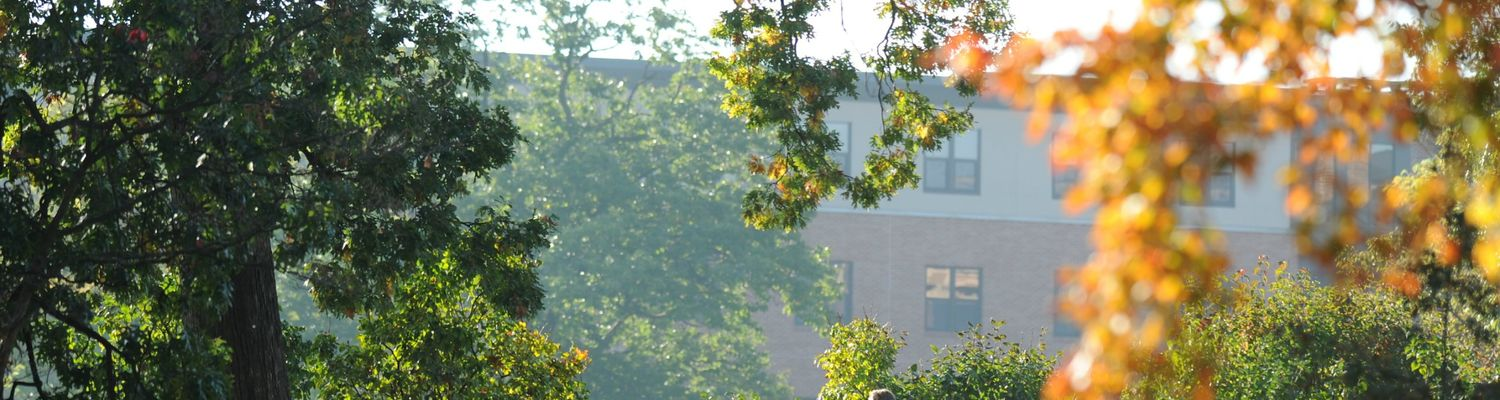 A faculty member walks across campus with a view of Johnson Hall in the background.