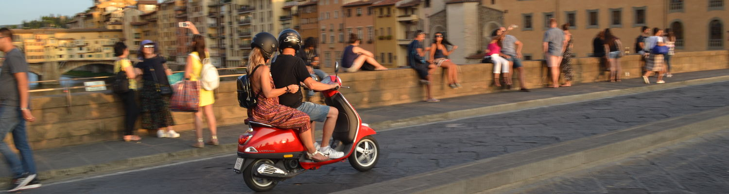 A Vespa speeds by in Florence