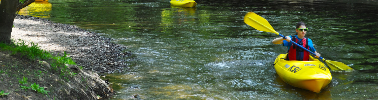 Students paddle down a river in kayaks