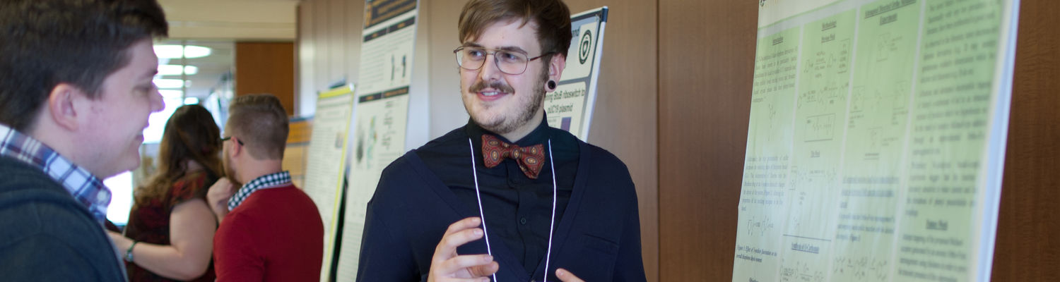 An undergraduate student presents his chemistry research results at a poster session.