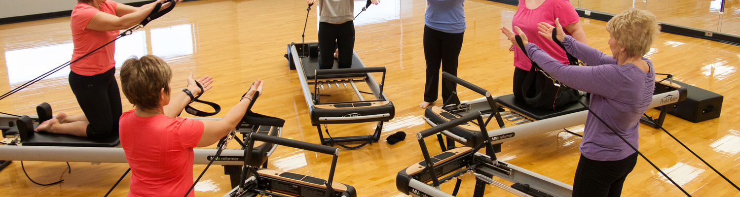 A group works out using stretch bands during a Reformer Pilates class