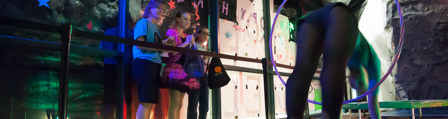A family watches a gymnast pass through a hoop in a Halloween-themed room at the Student Recreation and Wellness Center