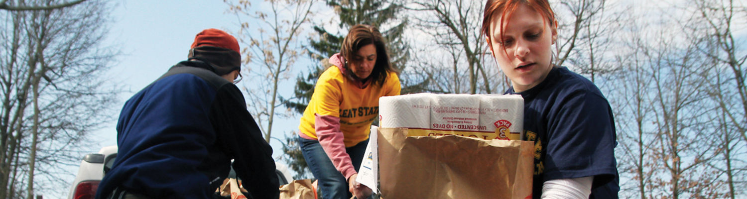 Student and staff carrying bags of donated items
