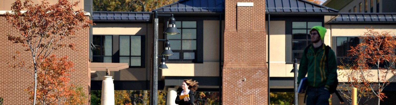 Students walk past the honors college on a fall day