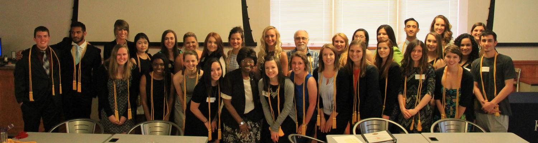 undergrad students pose after the lambda pi eta induction