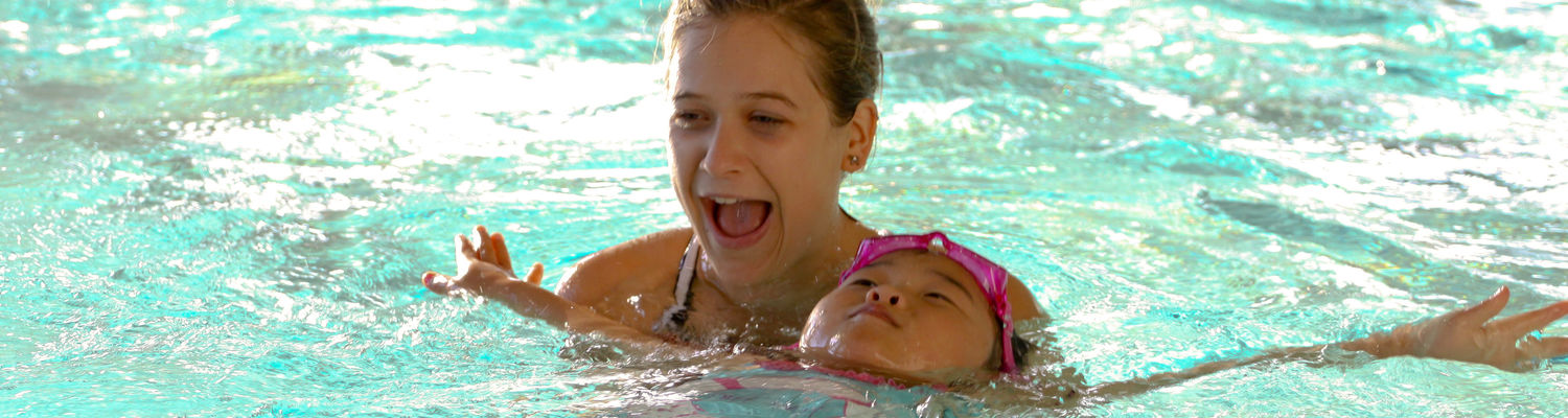 An instructor holds on to a child as they learn how to swim