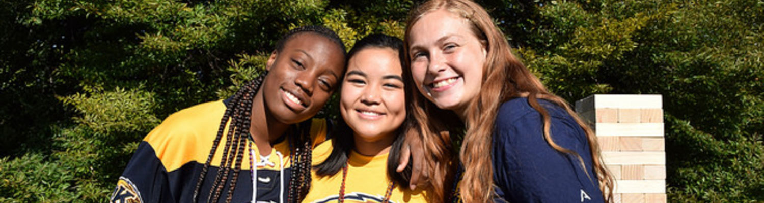 Three diverse students smiling