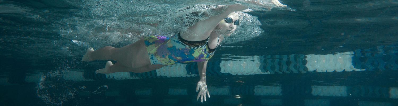 A student swims through one of the natatorium's lap pools