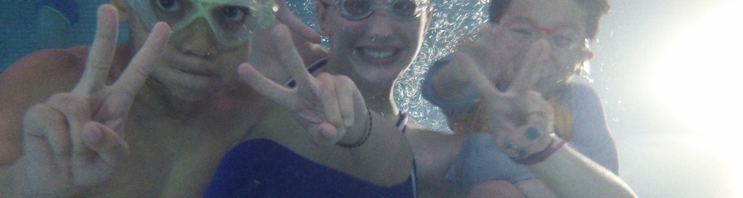 Kids smile and make V shapes with their fingers while underwater in one of the natatorium pools