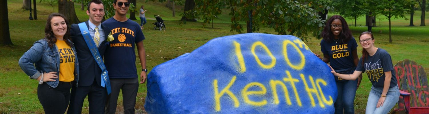 Students standing by the Spirit Rock painted with '100th Kent HC'