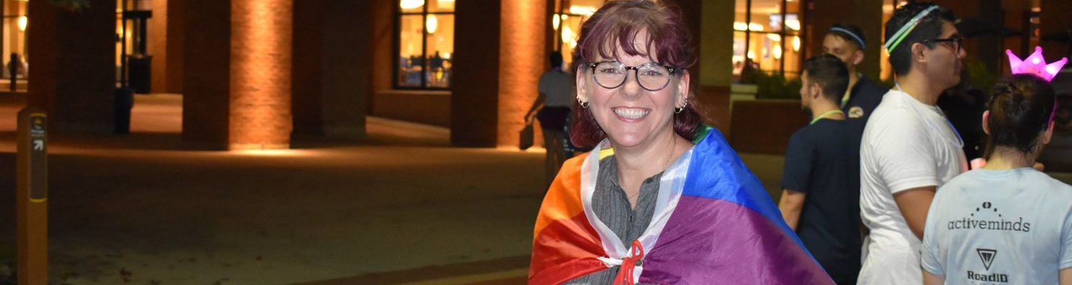 Female smiling with LGBTQ flag wrapped around her