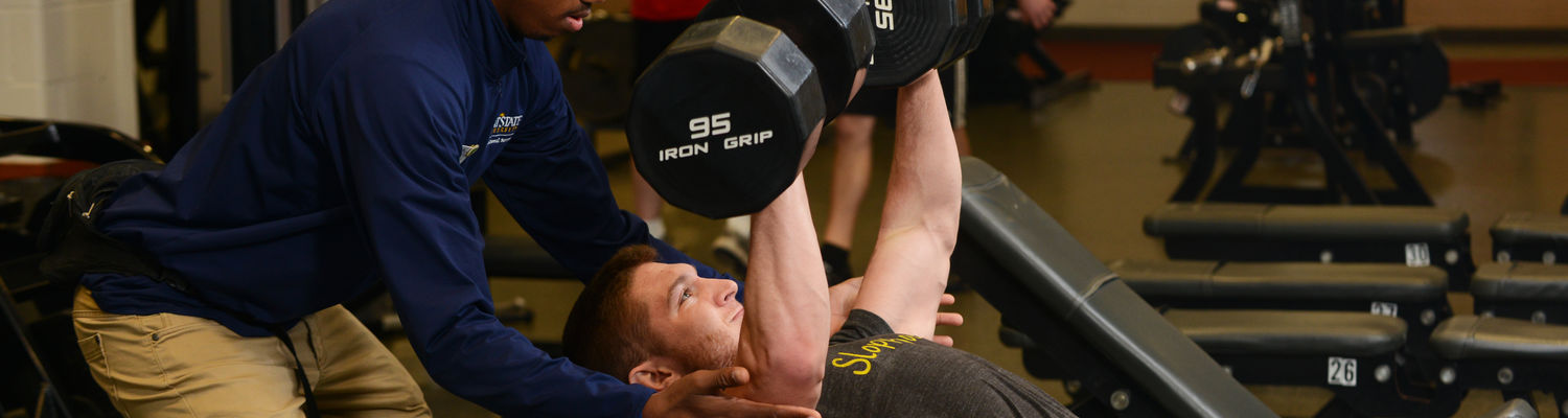 A trainer spots a student as they lift a pair of dumbbells over their head