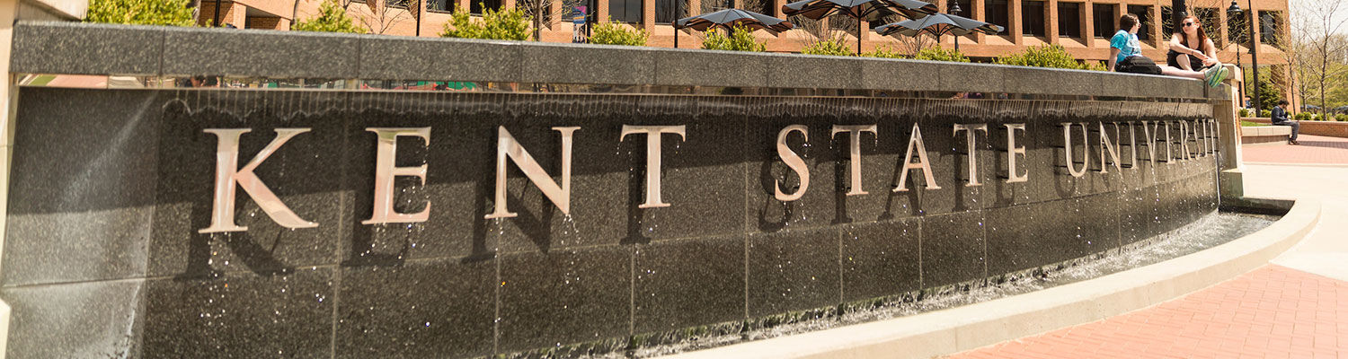 """A waterfall in front of the Kent Student Center with """"Kent State University"""" brass letters"""