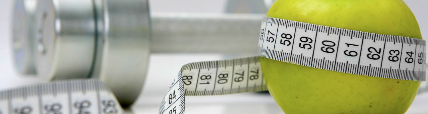 A pair of dumbbells sit behind an apple, which is wrapped in measuring tape
