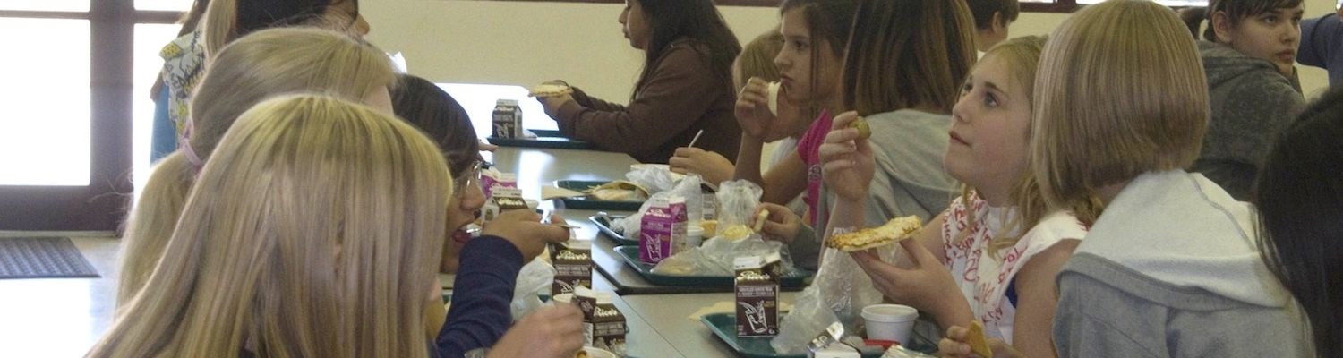 Teenagers sitting at a school lunch table