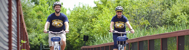 students biking on bridge smiling