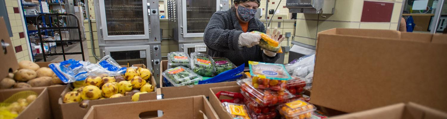 A volunteer packs food into boxes to give out