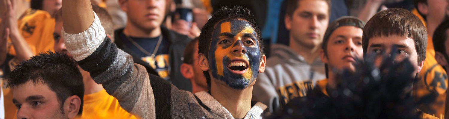 Students dressed in Kent State attire and face paint cheer on the Golden Flashes basketball team.