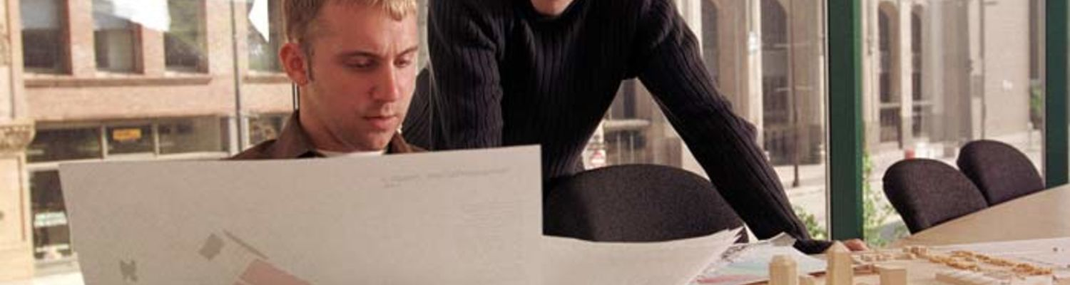 Two students look over architecture plans in an office conference room.