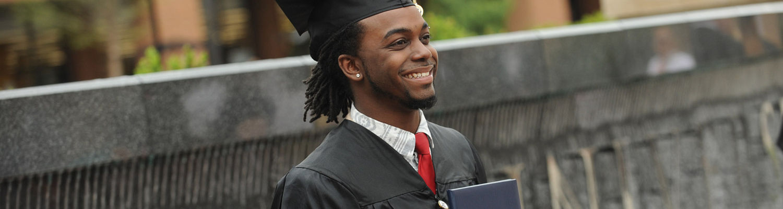 Graduate posing in Risman plaza
