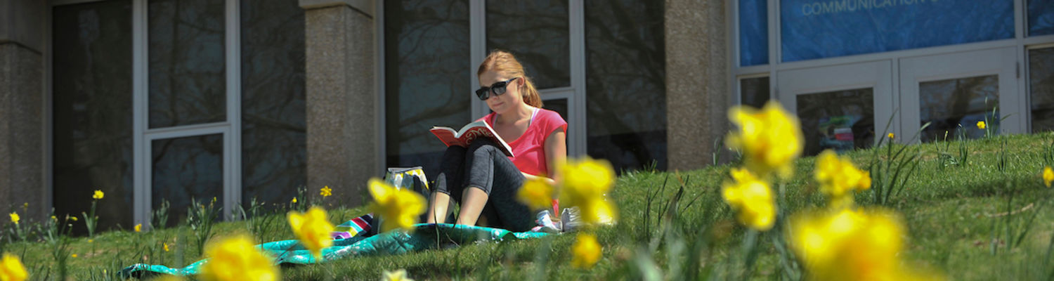 student seating on the grass reading