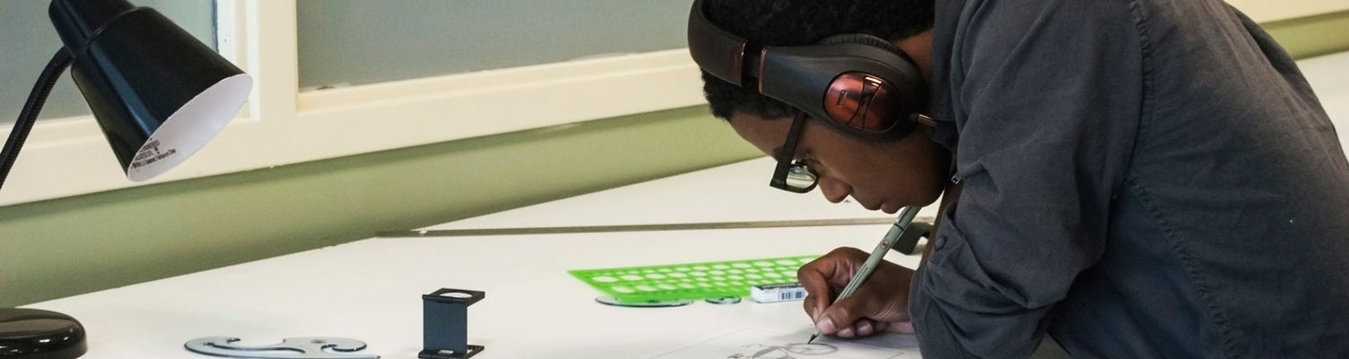 Student with headphones on works on a draft