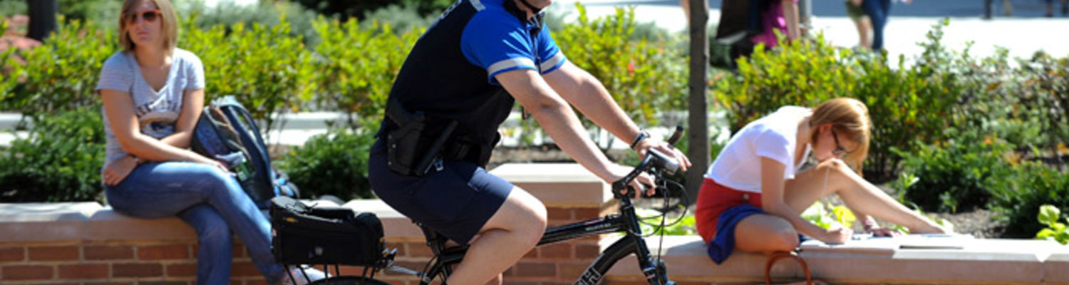 A police officer is patrolling on his bicycle around the student center plaza on a summer day.