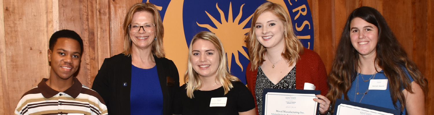 Scholarship winners standing with Dean at event