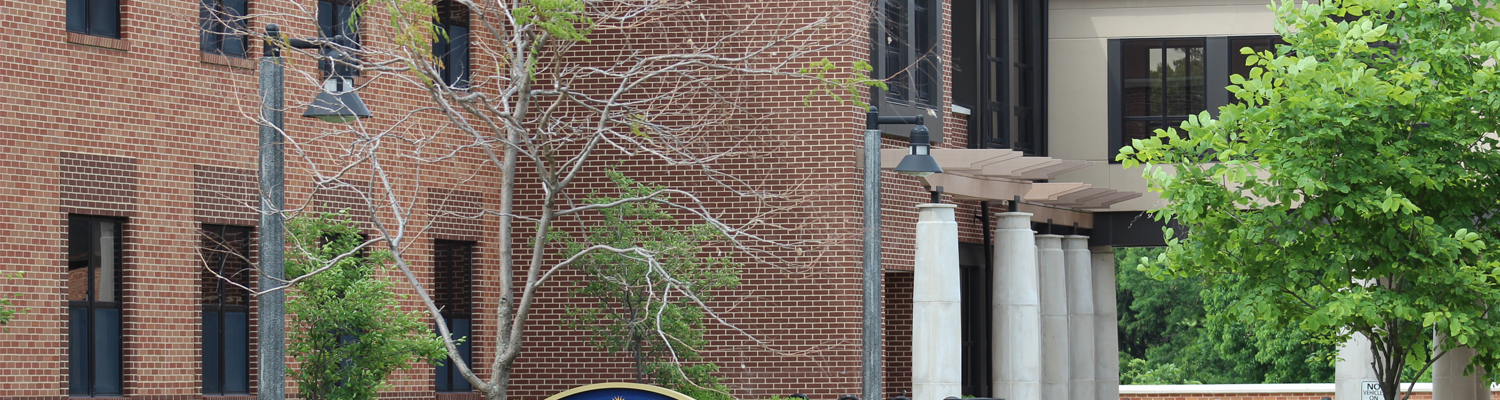 Outdoor view of Stopher Hall and entryway with building sign on display