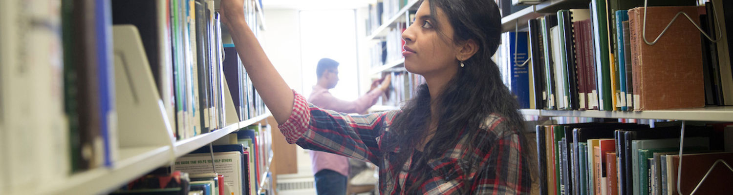 A student browses the shelves at University Library