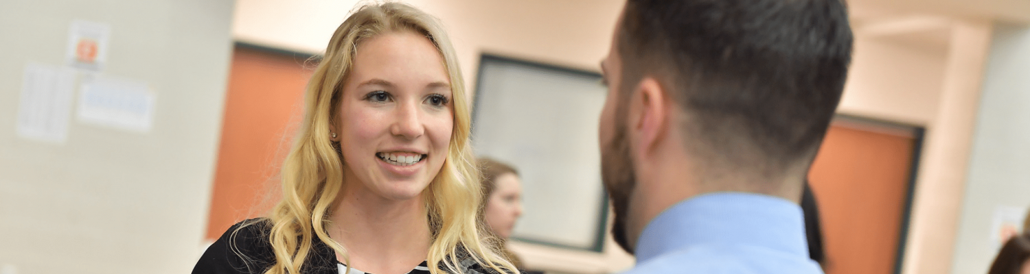 A smiling student talking to a businessperson at an event