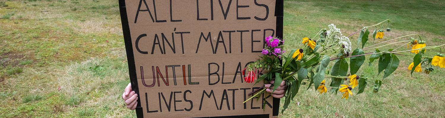 "A student holding a sign that reads, ""All lives can't matter until black lives matter."""