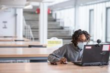 A student studies while wearing a mask