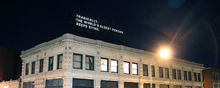 """Lenka Clayton, An Everyday Tragedy, 2016, A building with a billboard on top that reads in white letters """"Tragically, the world's oldest person keeps dying."""""""