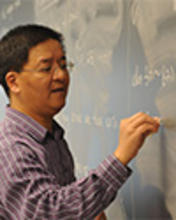 A faculty member uses a blackboard during lecture