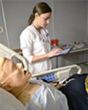 A student learns hands-on in the simulation lab with an electronic tablet and SimMan mannequin