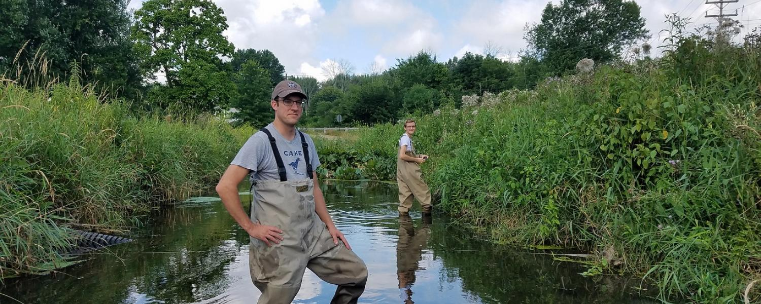 Dave Costello, Ph.D., (left), associate professor in Kent State University's Department of Biological Sciences in the College of Arts and Sciences, and Devan Mathie (right), an undergraduate honors student, stand in Wahoo Ditch in Ravenna, Ohio.