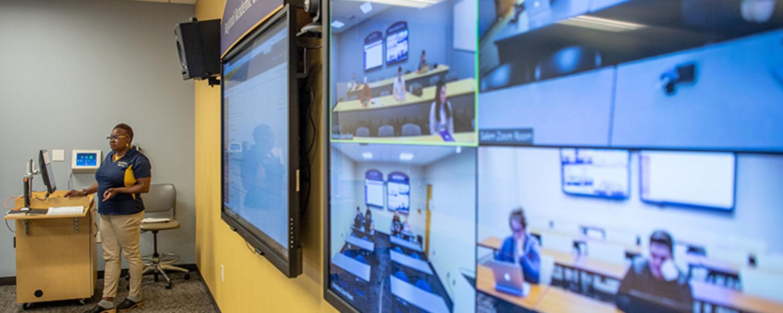 Professor teaching in Zoom class in front of tv screens