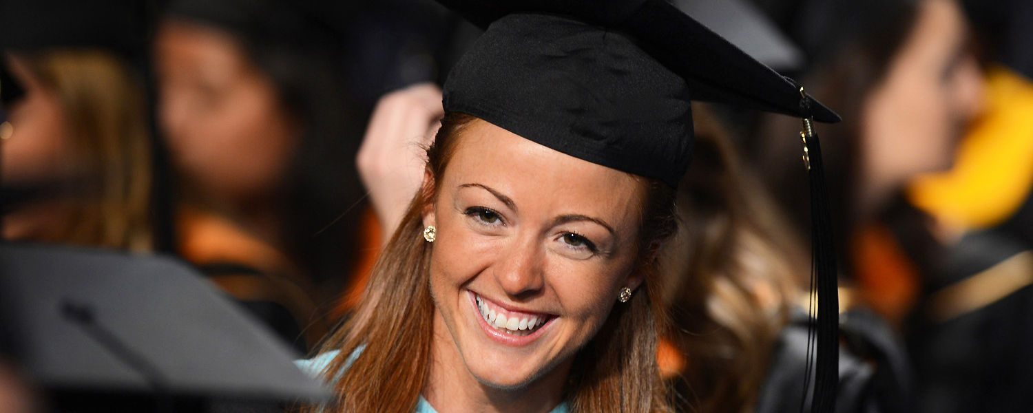 A Kent State graduate smiles to her friend during the Commencement ceremony on May 8.