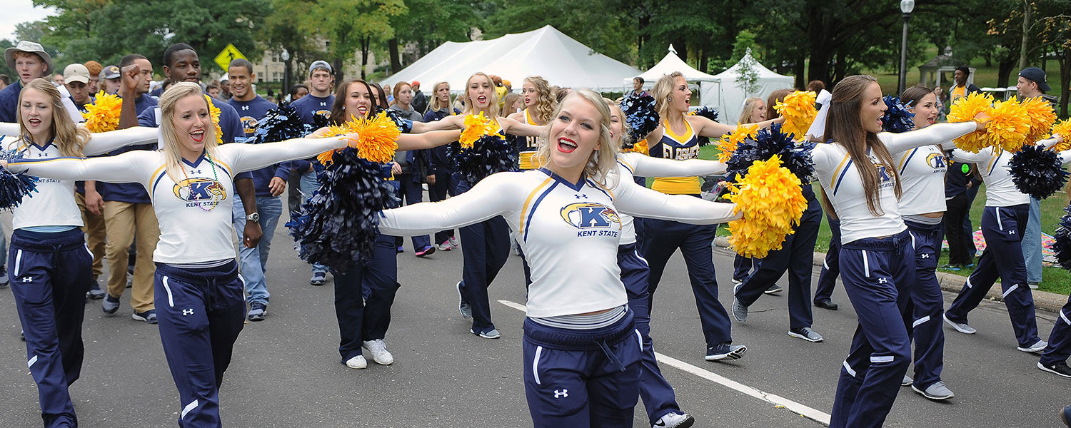 Kent State cheerleaders move past the new location for the Kent State Alumni tent, located at the Rock along Main Street, during the 2016 Homecoming Parade.
