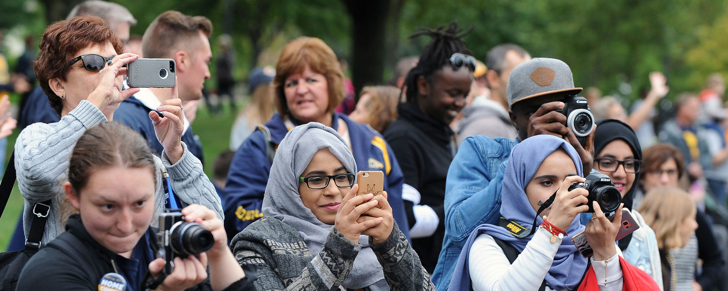 Students and local residents photograph floats participating in the 2016 Kent State Homecoming Parade as they pass by the grandstands on Main Street near Moulton Hall.