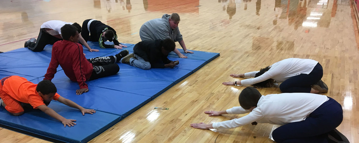 Kent State University College of Nursing seniors, Alyssa Lodi (back, right) and Anna Hunker (front, right), lead a group of middle school students through simple yoga stretches to promote relaxation and mindfulness during the health and wellness fair.